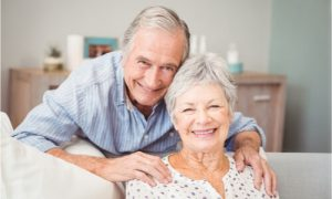 senior couple smiling with complete teeth