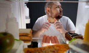 The man is secretly eating food.